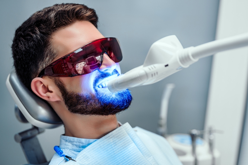 Man getting his teeth professionally whitened at a cosmetic dentist's office