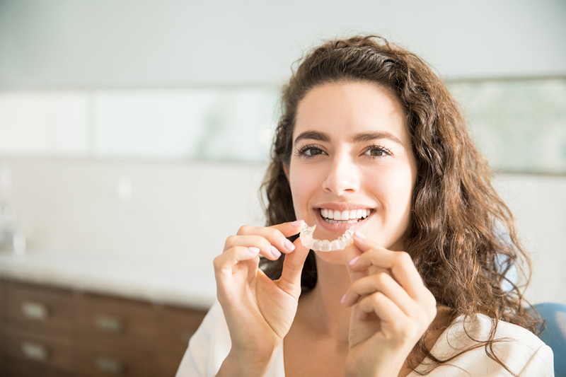 female patient holding orthodontic retainers like Invisalign