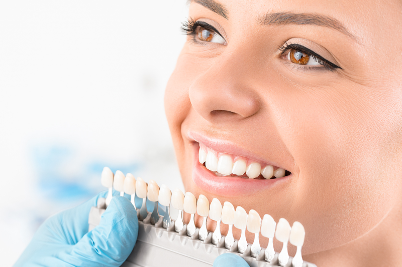 Beautiful smile and white teeth of a young woman getting fitted for cosmetic tooth crowns
