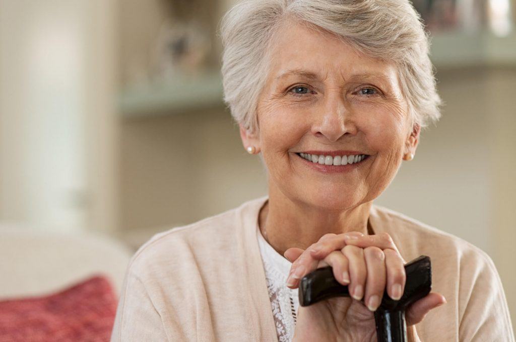 A senior woman with dentures smiling
