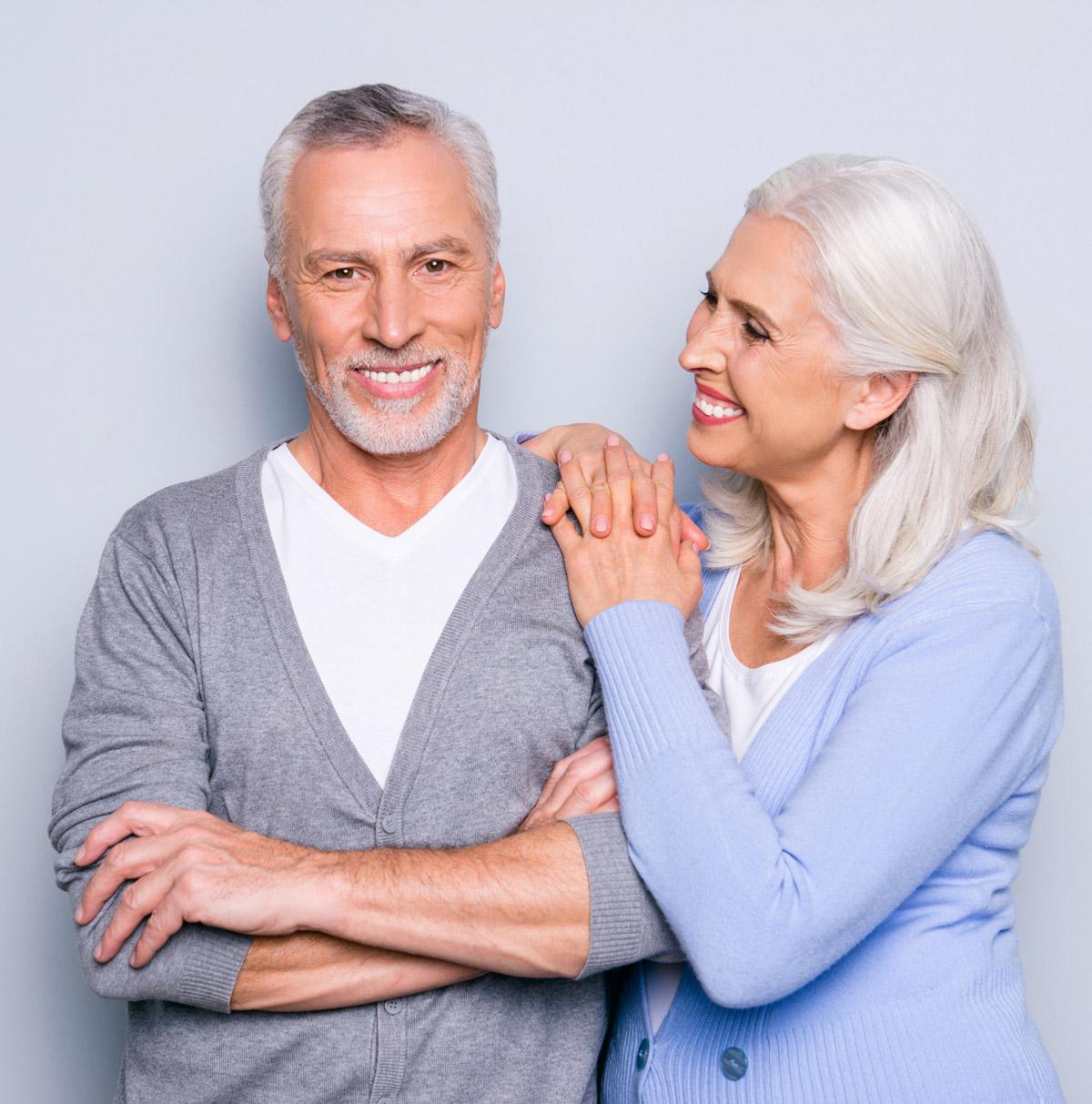 elderly couple smiling about affordable dental implants
