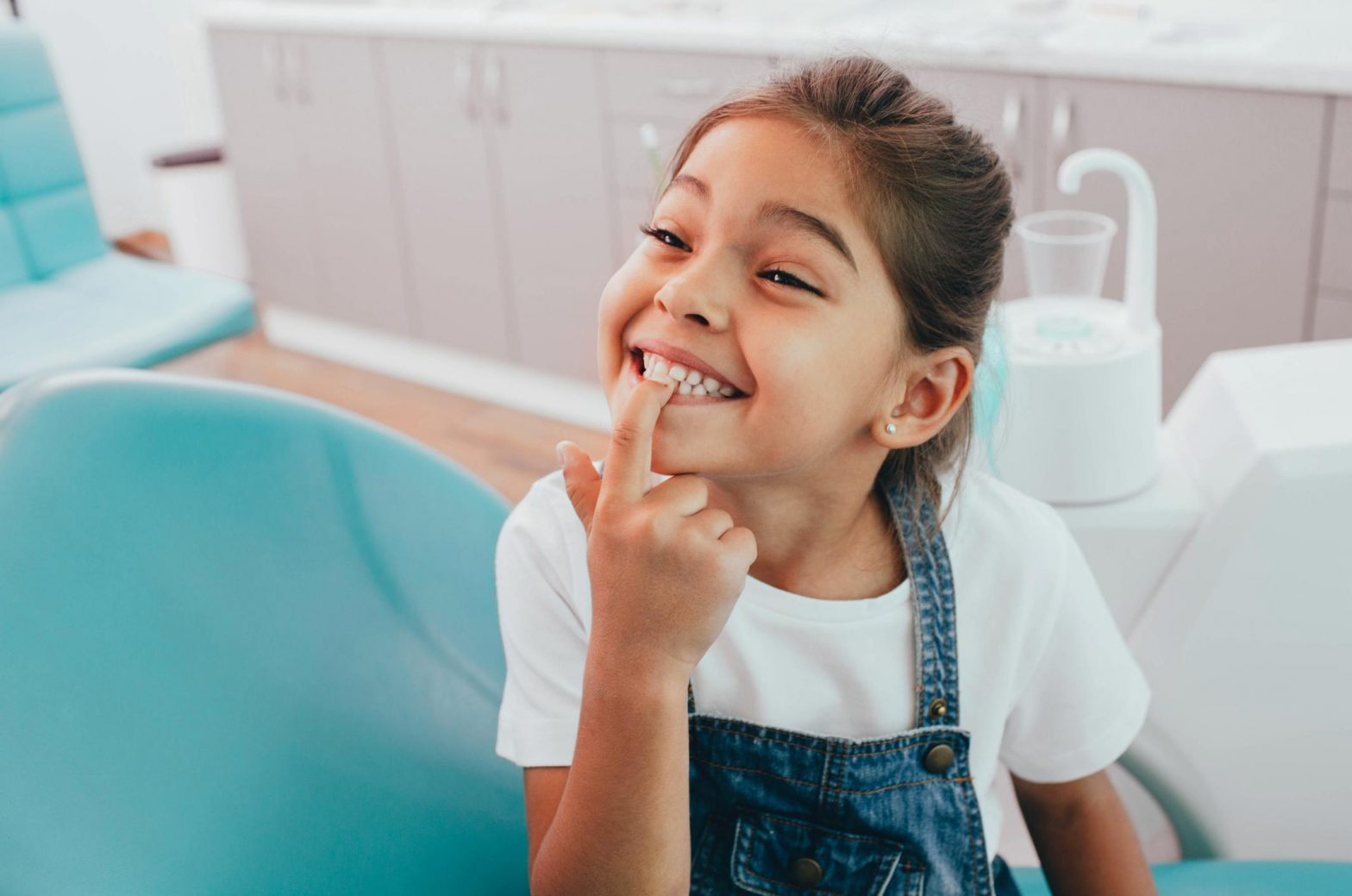 little girl showing her healthy teeth at a dental office