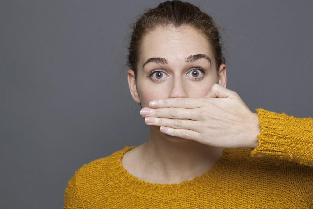 woman hiding her mouth because of halitosis or bad breath