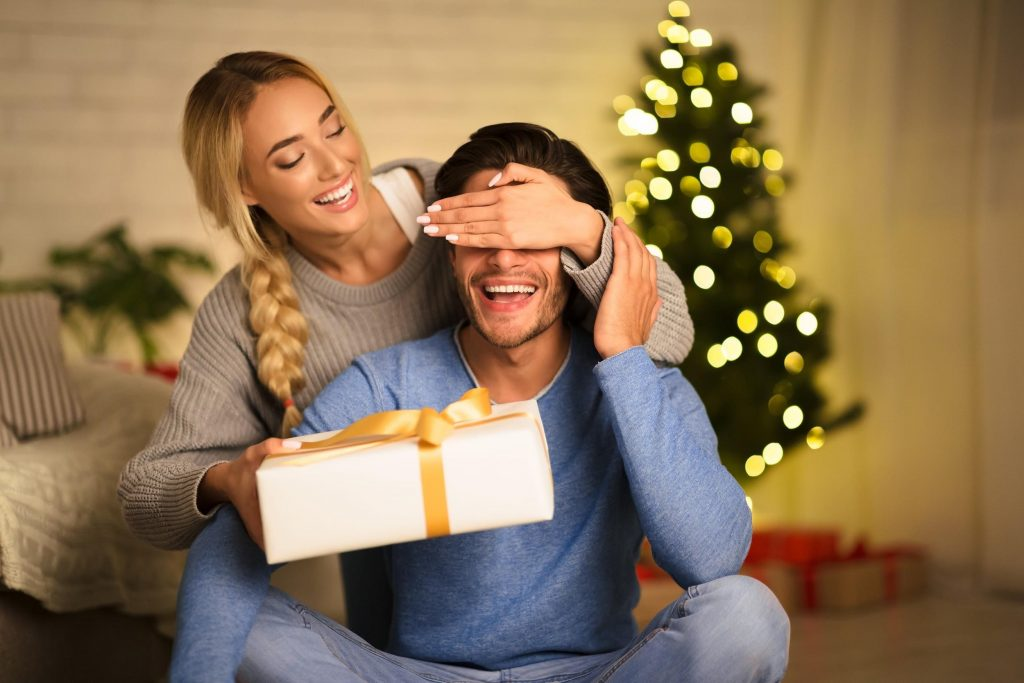 woman giving a man a gift of teeth whitening during the winter holidays