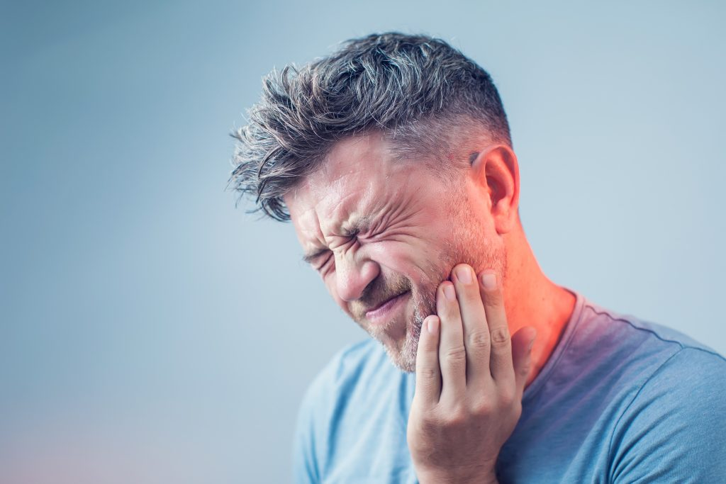 Man in pain with hand on cheek.